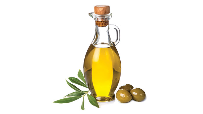 Bottle of oil, leaves and olives