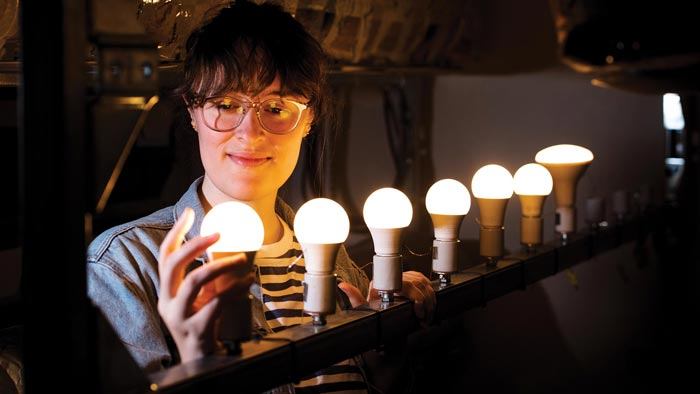 A student examines a rack of light bulbs
