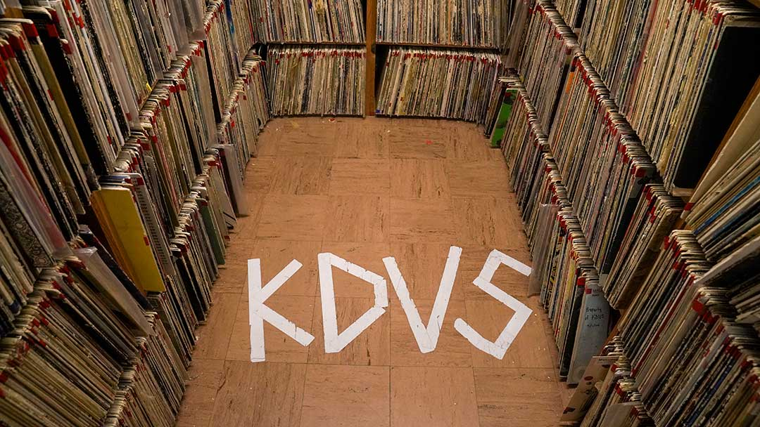Photo: stacks of records with KDVS spelled on the floor with tape