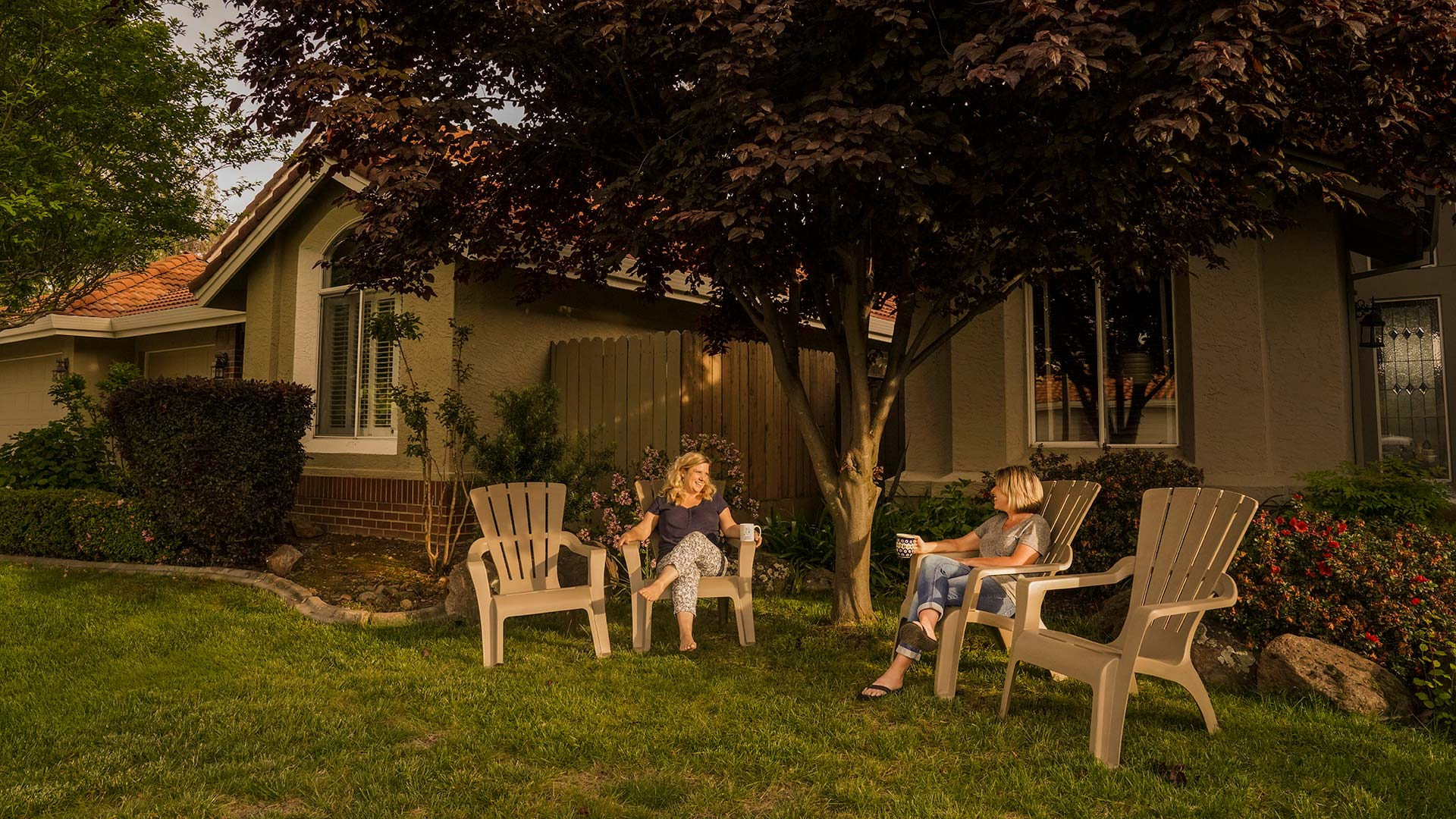 Two women sit and talk in lawn chairs in front of their houses.