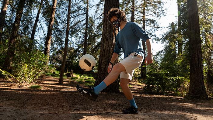 Ph.D. student Benjamin Faulkner kicks a soccer ball in the redwood grove