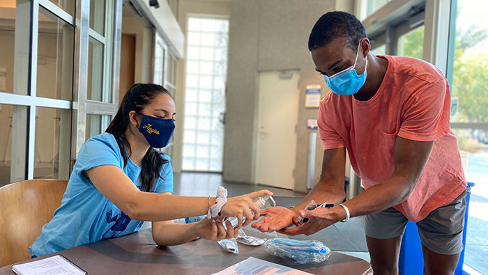 Student health ambassador dispenses hand sanitizer to another student
