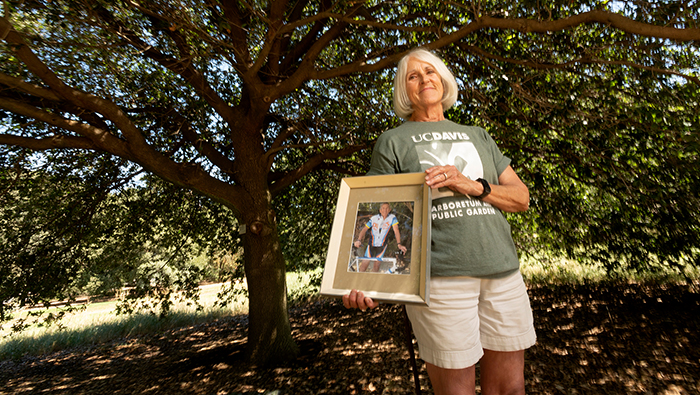 Nori Reinert holds a photo of her late husband William at the Arboretum