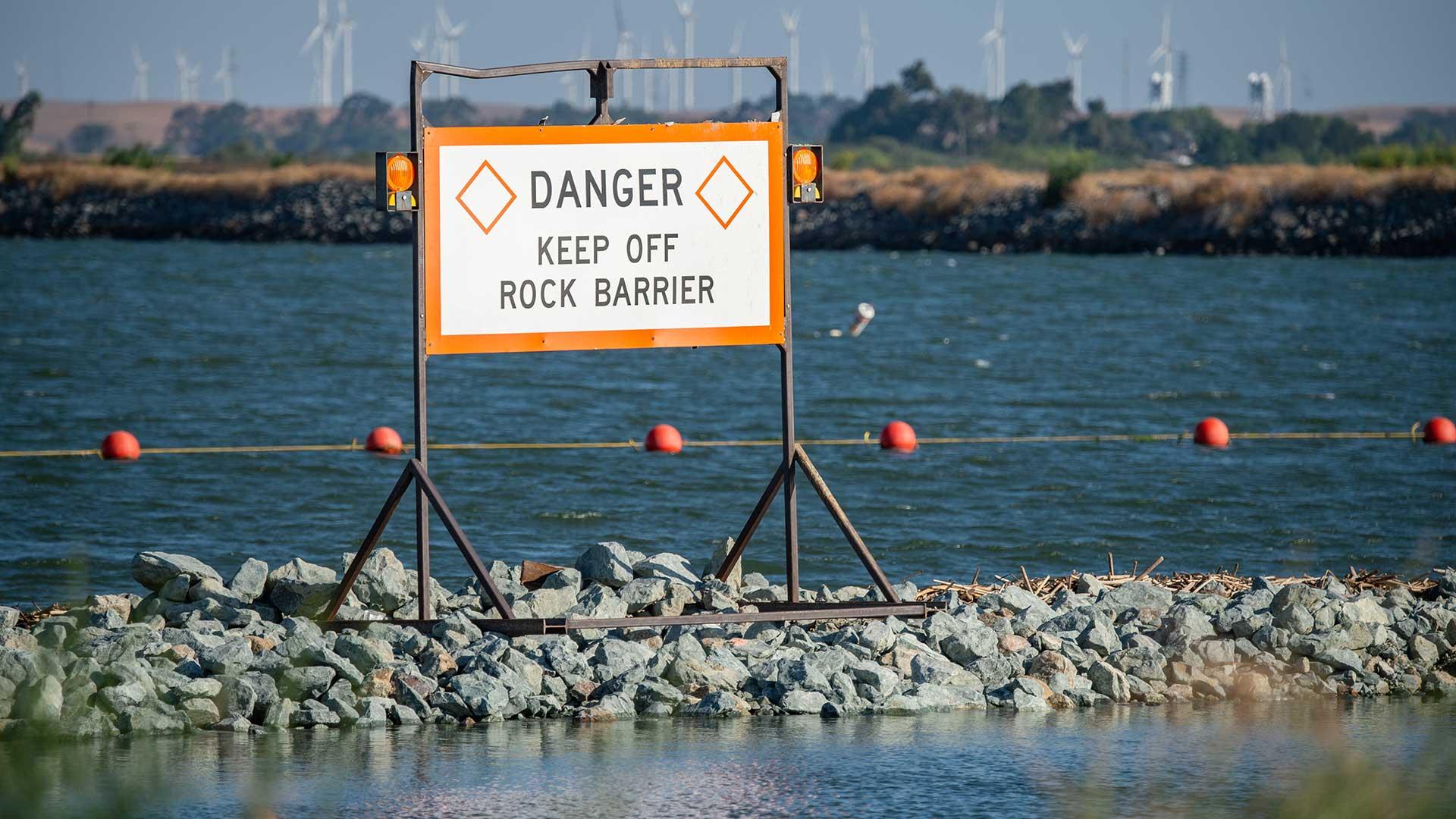 A rock barrier spans a river