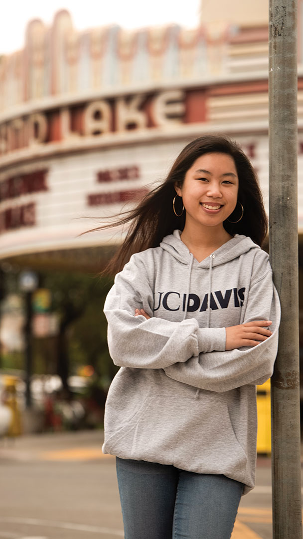 A student stands on a city street in front of a vintage theater