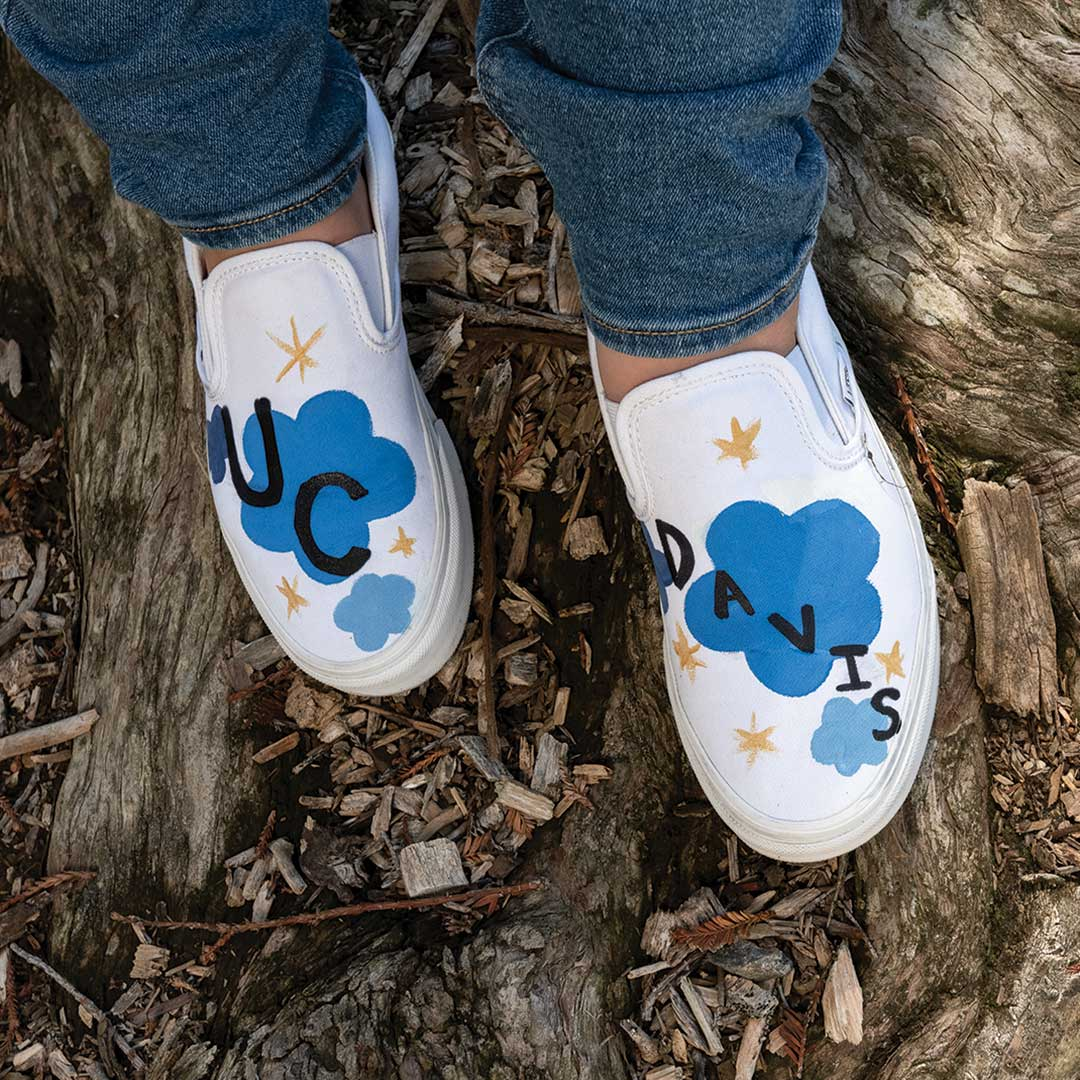 Shoes decorated with clouds, stars and the words UC Davis